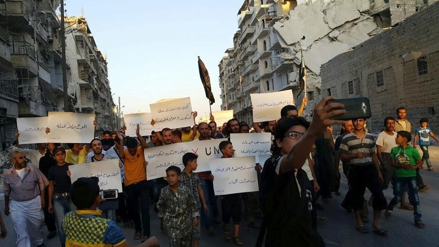 FILE - In this Sept. 13, 2016 file photo provided by Modar Shekho, activists in Syria's besieged Aleppo protest against the United Nations for what they say is its failure to lift the siege off their rebel-held area, in Aleppo, Syria. Residents in the rebel-held districts of Aleppo have a reprieve from the incessant bombings by Syrian government warplanes and the promise of an end to the crippling siege that has left produce stalls bare. (Modar Shekho via AP, File)