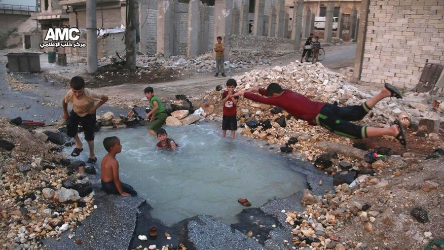 FILE -- This Aug. 31, 2016 file photo, provided by the Syrian anti-government activist group Aleppo Media Center (AMC), shows Syrian boys dive into a hole filled with water that was caused by a missile attack in the rebel-held neighborhood of Sheikh Saeed in Aleppo province, Syria. Residents in the rebel-held districts of Aleppo have a reprieve from the incessant bombings by Syrian government warplanes and the promise of an end to the crippling siege that has left produce stalls bare. (Aleppo Media Center via AP, File)
