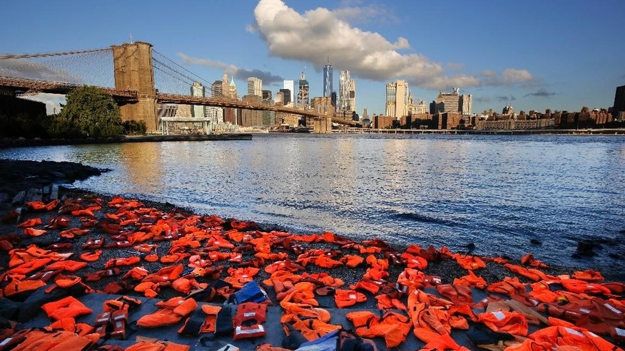 In this Sept. 16, 2016 file photo, hundreds of life jackets line the shore of the New York City waterfront in the Brooklyn borough of New York, placed there by advocates with Oxfam America to draw attention to the refugee crisis. Many of the life jackets used for the action had been collected on beaches in Greece after being  used by adult and child refugees. The undertaking was a prelude to the United Nations Summit for Refugees and Migrants. The question of what to do about the world's 65.3 million displaced people takes center stage at the UN General Assembly Monday, Sept. 19, when leaders from around the globe converge on New York for the first-ever summit on Addressing Large Movements of Refugees and Migrants. (AP Photo/Mark Lennihan, File)