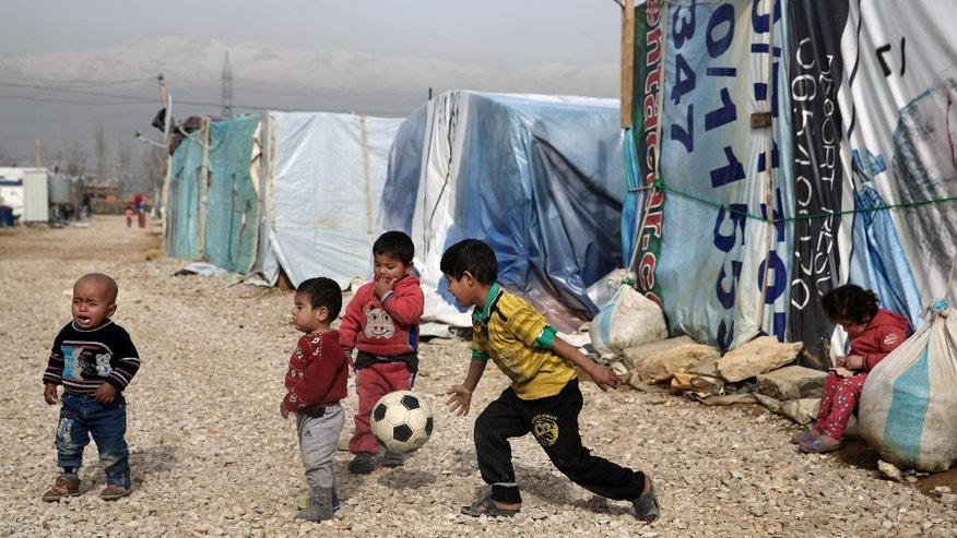 FILE - In this Jan. 22, 2016 file photo, Syrian refugee children play outside their family tents in a camp in the town of Saadnayel, in the Bekaa valley, Lebanon. The question of what to do about the world's 65.3 million displaced people takes center stage at the United Nations General Assembly Monday, Sept. 19, 2016, when leaders from around the globe converge on New York for the first-ever summit on Addressing Large Movements of Refugees and Migrants. (AP Photo/Bilal Hussein, File)