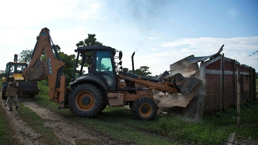 Authorities demolish houses at Bandardubi village on the periphery of the Kaziranga National Park, northeastern Assam state, India, Monday, Sept. 19, 2016. Authorities ordered the demolition of around 300 houses in three villages to evict people living on the periphery of the rhino sanctuary to stop rampant poaching of the rare animal, a top police official said. Two people were killed and several others were injured Monday when villagers clashed with police while protesting the demolition of their homes. (AP Photo/Anupam Nath)