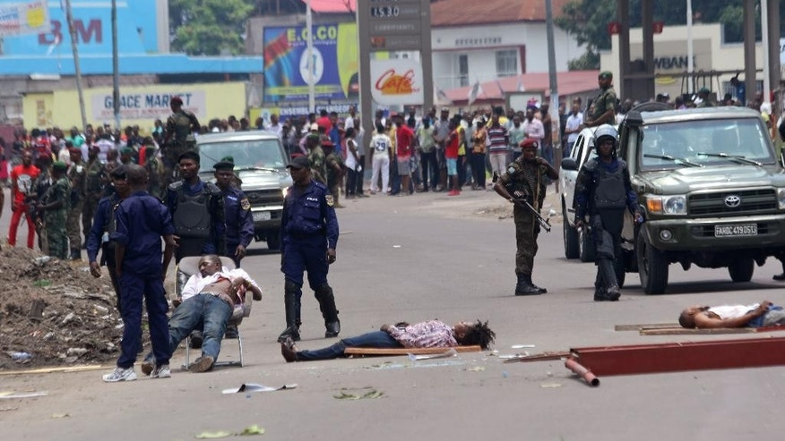The bodies of people killed during election protests lie in the street, as Congolese troops stand near by in Kinshasa, Democratic Republic of Congo, Monday, Sept. 19, 2016. Witnesses say at least four people are dead after opposition protests against a delayed presidential election turned violent in Congo's capital. The protests were organized by activists who are opposed to longtime President Joseph Kabila, who is now expected to stay in office after his mandate ends in December. (AP Photo/John Bompengo)