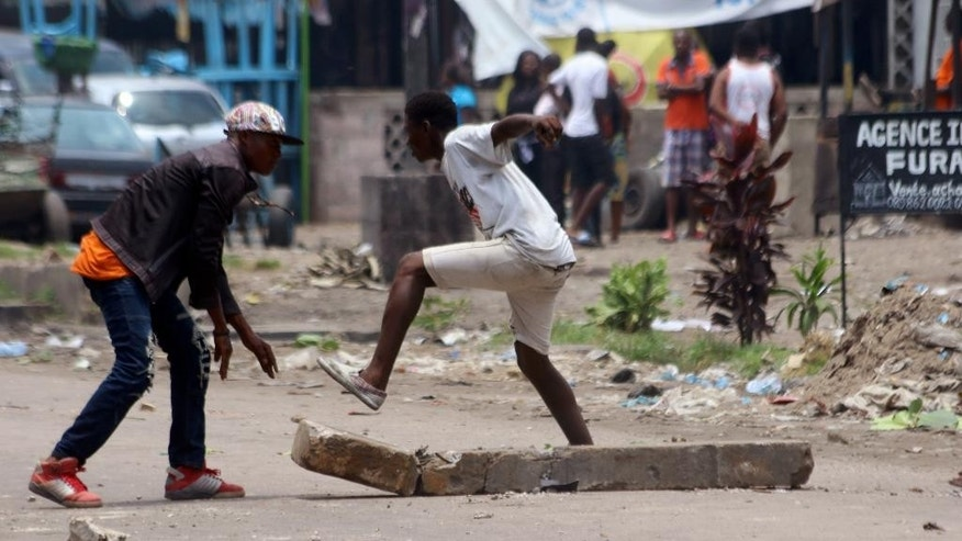 Men break off bits of rock during a protest in Kinshasa in Kinshasa, Democratic Republic of Congo, Monday, Sept. 19, 2016. Witnesses say at least four people are dead after opposition protests against a delayed presidential election turned violent in Congo's capital. The protests were organized by activists who are opposed to longtime President Joseph Kabila, who is now expected to stay in office after his mandate ends in December. (AP Photo/John Bompengo)