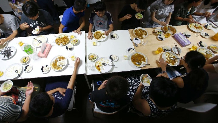 """In this Aug. 18, 2016 photo, visitors and volunteers have a meal at a """"children's cafeterias,"""" in Tokyo. Many people in Japan are helping kids facing hardships by setting up """"children's cafeterias"""" where students can dine and relax with their neighbors. Poverty in Japan is largely hidden. Families often skimp on food and other necessities to ensure children are dressed well enough to avoid being seen as disadvantaged. (AP Photo/Shizuo Kambayashi)"""