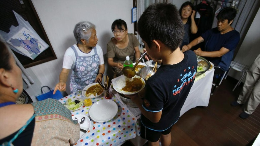 """In this Aug. 18, 2016 photo, a boy ladles curry into a plate at a """"children's cafeterias"""" started by Misako Omura in Tokyo.  Omura's weekly dinner is one of a growing number of """"kodomo shokudo,"""" or """"children's cafeterias,"""" that are springing up across Japan. The mostly grassroots efforts seek to address a range of child-related issues, from poverty to ensuring that those with late-working parents get a proper dinner.   (AP Photo/Shizuo Kambayashi)"""