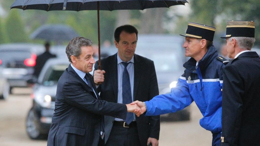 Former French President Nicolas Sarkozy, left, shakes hands with a Gendarme as he arrives to a ceremony for victims of terrorism in Paris, Monday Sept.19, 2016. French President Francois Hollande presides over a national ceremony to pay tribute to victims of terrorist attacks including that targeting Nice on Bastille Day. (AP Photo/Michel Euler, Pool)