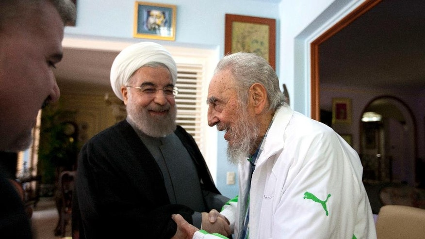 Cuba's former leader Fidel Castro, right, shakes hands with Iranian President Hassan Rouhani, center, in Havana, Cuba, Monday, Sept 19, 2016. Rouhani is on a one-day official visit to Cuba. (AP Photo/Alex Castro)