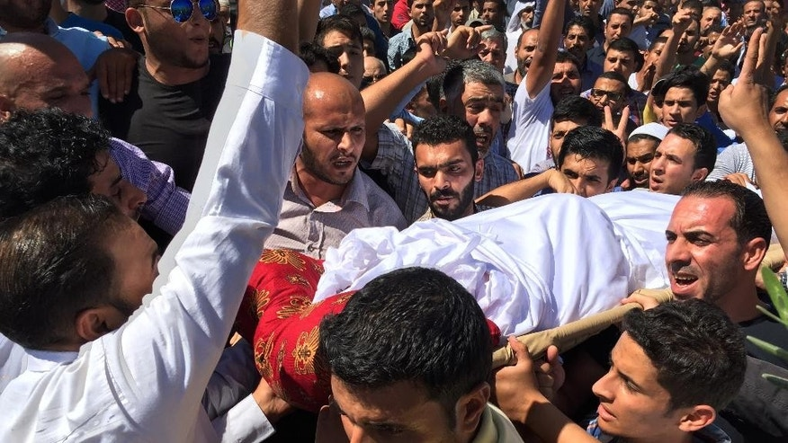 "Men carry the body of Said Amro during his funeral in his hometown of Al-Mogheer, Jordan, Monday, Sept. 19, 2016. Jordan has demanded a detailed explanation from Israel about the killing of Amro, a 28-year-old Jordanian, by Israeli troops last week. Hundreds attended Amro's funeral, chanting ""Death to Israel."" Israeli police have said Said Amro came out of a gate of Jerusalem's Old City with a knife in each hand, shouted ""God is Great"" and rushed at officers before being shot dead. (AP Photo/Omar Akour)"