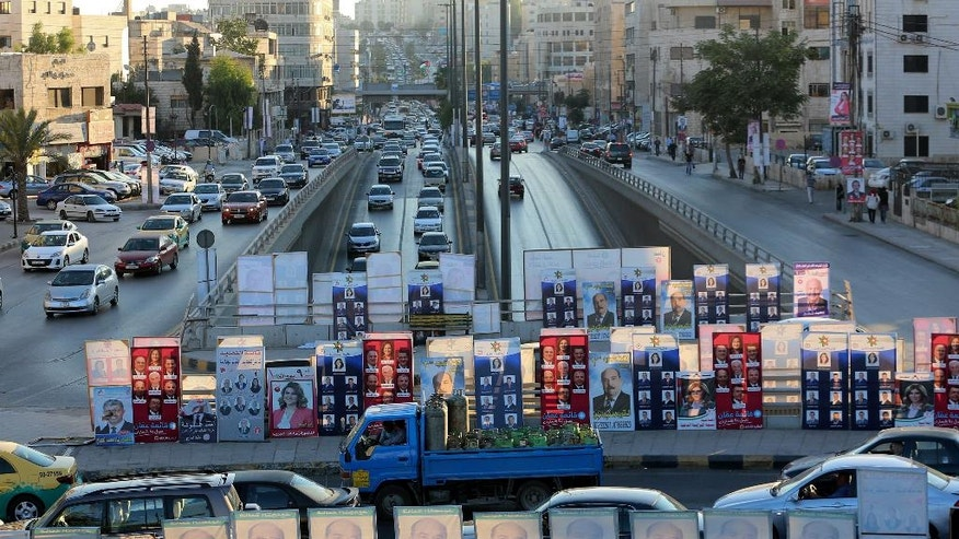 Election posters are on display in the capital, Amman, Jordan, Sunday, Sept. 18, 2016. Officials say Jordan's upcoming parliament election shows that the pro-Western monarchy is moving forward with democratic reforms, while critics argue that new voting rules have fallen short and won't deliver change. In Tuesday's vote, more than 1,200 candidates compete for 130 seats and the largest opposition group, the Muslim Brotherhood, participates for the first time in almost a decade. (AP Photo/Raad Adayleh)
