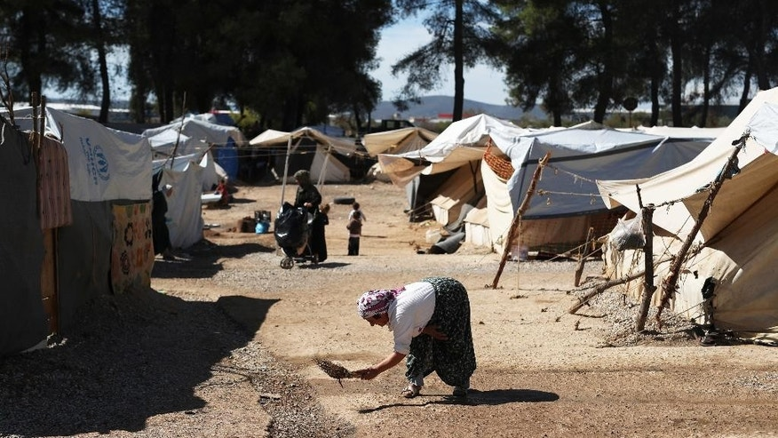 A woman sweeps a path among the tents at the Ritsona refugee camp north of Athens, which hosts about 600 refugees and migrants on Monday, Sept. 19, 2016. The European Union's border agency says the number of migrants arriving in the Greek islands has increased significantly over the last month. (AP Photo/Petros Giannakouris)