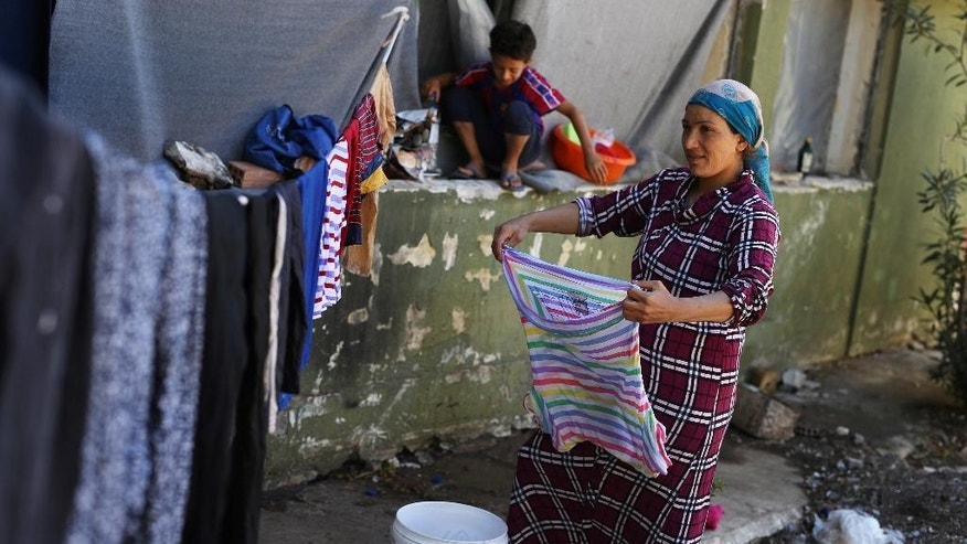 A Syrian Kurdish woman hangs out washing at Ritsona refugee camp north of Athens, which hosts about 600 refugees and migrants on Monday, Sept. 19, 2016. The European Union's border agency says the number of migrants arriving in the Greek islands has increased significantly over the last month.(AP Photo/Petros Giannakouris)