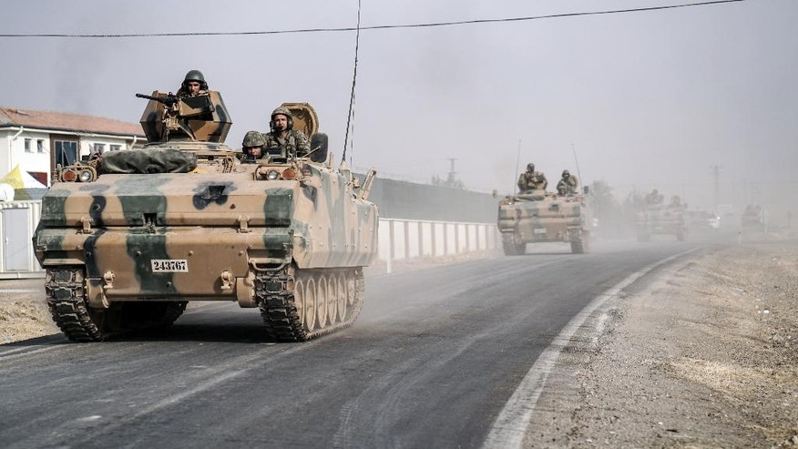 FILE- In this Thursday, Aug. 25, 2016 file photo, Turkish army tanks and armored personnel carriers move toward the Syrian border, in Karkamis, Turkey. Last month, Turkey for the first time sent tanks across the border into Syria to help rebels clear territory of IS militants and to contain the  expansion of a Syrian Kurdish militia. (AP Photo/Halit Onur Sandal, File)