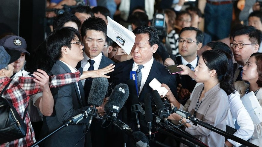 An unidentified man, left, hurls papers to Lotte Group's Chairman Shin Dong-bin, center, as he arrives to undergo questioning over suspected embezzlement at the Seoul Central District Prosecutors' Office in Seoul, South Korea, Tuesday, Sept. 20, 2016.   Shin was summoned to Seoul District Public Prosecutor's Office on Tuesday to be questioned over allegations of malpractice and embezzlement involving his group. (AP Photo/Ahn Young-joon)