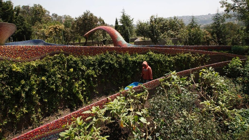 """In this Wednesday, Sept. 14, 2016 photo, a gardener pushes a wheelbarrow on the grounds of the architectural project, the """"Nest of Quetzalcoatl,"""" on the outskirts of Mexico City. Architect Javier Senosiain sinuous snake's nest of a building weaves through a green and tranquil vista on the very edge of Mexico's urban sprawl. (AP Photo/Marco Ugarte)"""