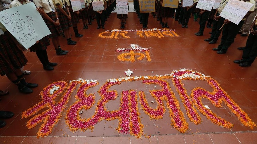"Indian students hold placards and stand near a formation of flowers that read ""tribute to brave martyrs"" as they pay tribute to the Indian soldiers killed in the Sunday attack on army base in Indian-controlled Kashmir early Sunday, at a school in Ahmadabad, India, Monday, Sept. 19, 2016. Suspected rebels using guns and grenades sneaked into a crucial army base in Indian-controlled Kashmir early Sunday and killed at least 17 soldiers in the deadliest attack on a military base in the disputed Himalayan region in recent years, the army said. (AP Photo/Ajit Solanki)"