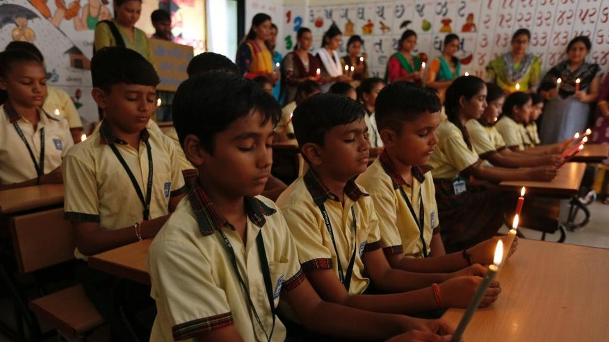 Indian students and teachers holds candles as they pay tribute to the Indian soldiers killed in the Sunday attack on army base in Indian-controlled Kashmir, at a school in Ahmadabad, India, Monday, Sept. 19, 2016. Suspected rebels using guns and grenades sneaked into a crucial army base in Indian-controlled Kashmir early Sunday and killed at least 17 soldiers in the deadliest attack on a military base in the disputed Himalayan region in recent years, the army said. (AP Photo/Ajit Solanki)