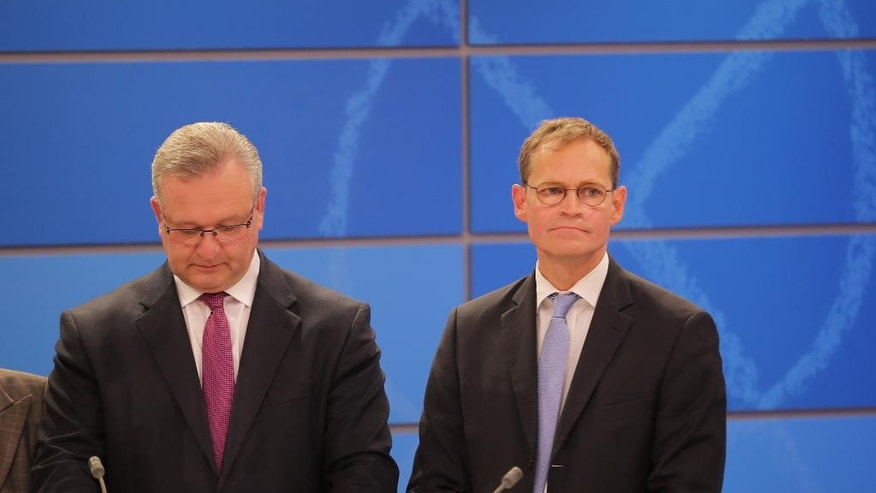 The top candidates of the Christian Democrats, Frank Henkel, left, and Social Democrats, Mayor Michael Mueller, wait for the beginning of a telecast after the state elections in the German capital Berlin Sunday, Sept. 18, 2016. (Michel Kappeler/dpa via AP)