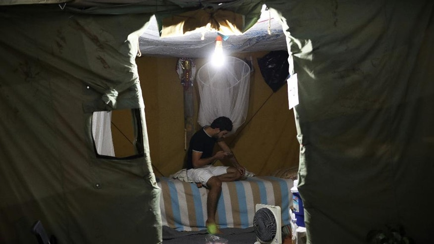 In this photo taken on Tuesday, Sept. 13, 2016, a Syrian man looks at his mobile phone inside his tent at Ritsona refugee camp north of Athens. Most of the people at the camp arrived in Greece in March, crossing to Lesbos and Chios just ahead of an agreement between the EU and Turkey that took effect. Under the deal, anyone arriving on Greek islands from Turkey on or after March 20 would be held on the island and face being returned to Turkey. Balkan countries began restricting crossings of their borders in early 2016, and shut them completely in early March, stranding tens of thousands of people in Greece. (AP Photo/Petros Giannakouris)