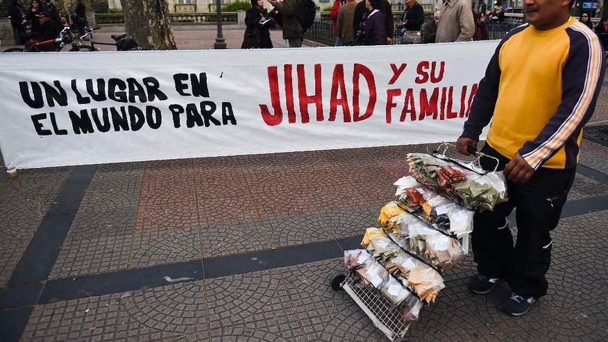 "A street vendor passes a sign that reads in Spanish ""A place in the world for Jihad and his family""  placed by demonstrators in downtown Montevideo, Uruguay, Friday, Sept. 16, 2016. Former Guantanamo detainee Abu Wa'el Dhiab from Syria, also called Jihad, is on a hunger strike, threatening to die if he is not allowed to reunite with his family elsewhere, after he was resettled in Uruguay. (AP Photo/Matilde Campodonico)"