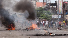 People stand near burning debris during election protests in Kinshasa, Democratic Republic of Congo, Monday, Sept. 19, 2016. Witnesses say at least four people are dead after opposition protests against a delayed presidential election turned violent in Congo's capital. The protests were organized by activists who are opposed to longtime President Joseph Kabila, who is now expected to stay in office after his mandate ends in December. (AP Photo/John Bompengo)