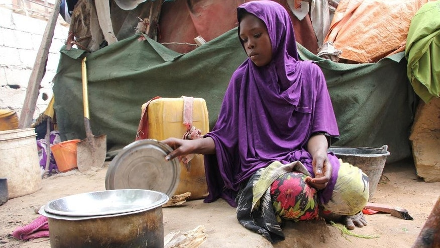 Somali young girl cooks food outside their makeshift home inside a refugee camp in Mogadishu, Somalia, Tuesday, Sept. 20, 2016.   A new U.N. report says five million people, more than 40 percent of the population in Somalia, are not getting enough food, on the chaotic Horn of Africa. The report released Tuesday says the number of people who are food insecure has increased by 300,000 since February.  (AP Photo/Farah Abdi Warsameh)