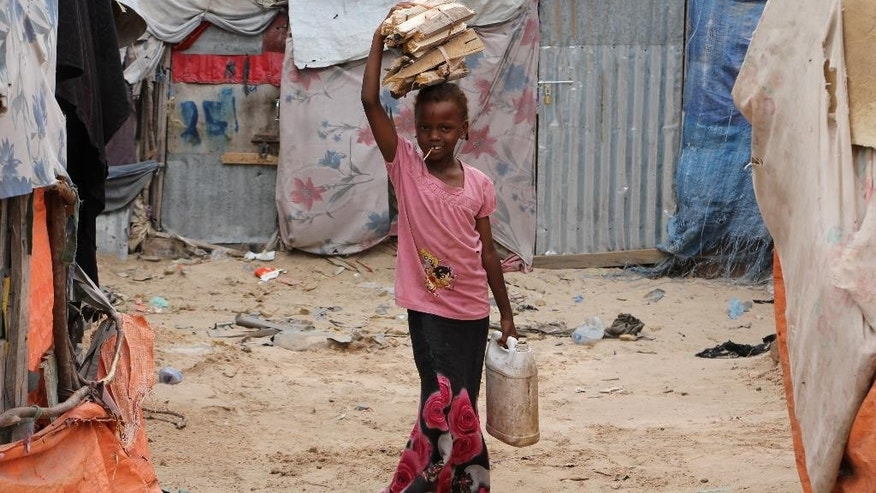 A Somali refugee girl carries firewood on her head as she makes her way back to her makeshift home inside a refugee camp in Mogadishu, Somalia, Tuesday,Sept,20, 2016. A new U.N. report says five million people, more than 40 percent of the population in Somalia, are not getting enough food, on the chaotic Horn of Africa. The report released Tuesday says the number of people who are food insecure has increased by 300,000 since February.  (AP Photo/Farah Abdi Warsameh)