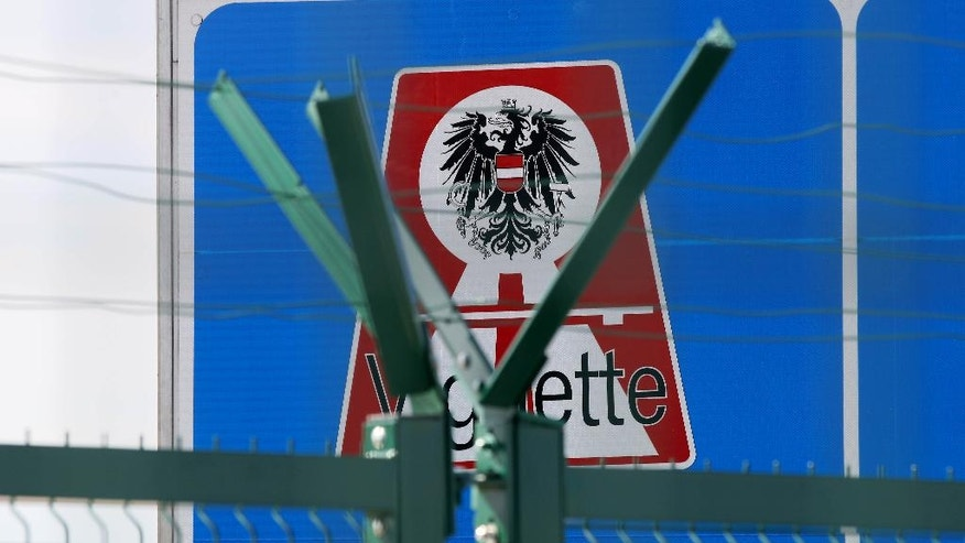 The Austrian state coat of arms behind a newly erected fences on the border between Hungary and Austria in Nickelsdorf, Austria, Tuesday, Sept. 20, 2016. (AP Photo/Ronald Zak)
