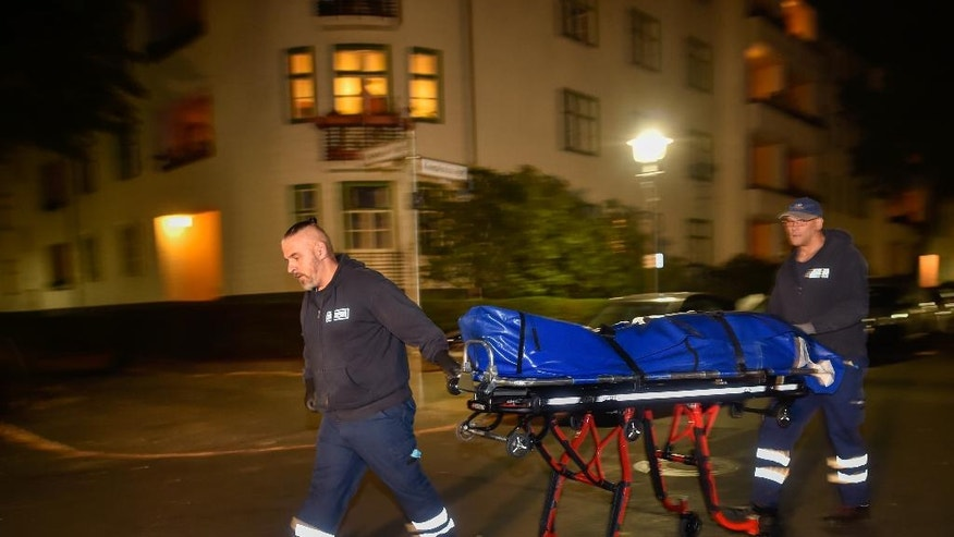 In this Sept. 19, 2016 photo coroner's workers carry a corpse to transportation from the residence of Pirate politician Gerwald Claus-Brunner in Berlin, Germany. Two people were found dead in his flat. (Klaus-Dietmar Gabbert/dpa via AP)
