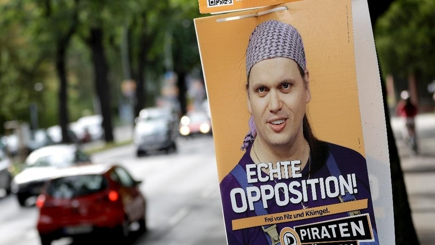 Cars pass by an election campaign poster of the state parliament member Gerwald Claus-Brunner of the 'Piraten' (Pirates) party in Berlin, Germany, Tuesday, Sept. 20, 2016. Berlin officials say a member of the city's Pirate Party was found dead in his apartment along with the body of another man and that homicide detectives are investigating. (AP Photo/Michael Sohn)