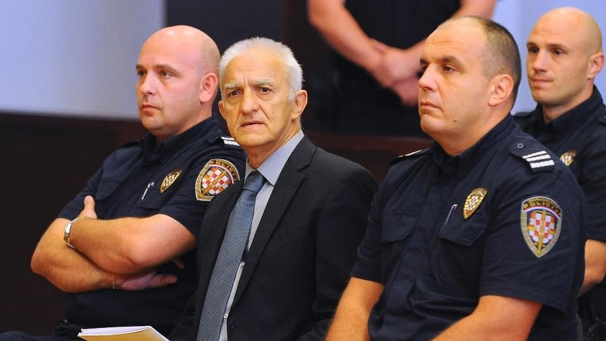 Dragan Vasiljkovic, center, a former Serb military commander, sits between two guards in a courtroom at the beginning of his trial in Split, Croatia, Tuesday, Sept. 20, 2016. Vasiljkovic is accused of overseeing the torture and murder of civilians and prisoners in Croatia in the early 1990s. (AP Photo)