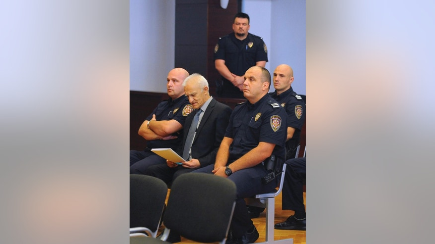Dragan Vasiljkovic, center, a former Serb military commander sits between guards in a courtroom at the beginning of his trial in Split, Croatia, Tuesday, Sept. 20, 2016. Vasiljkovic is accused of overseeing the torture and murder of civilians and prisoners in Croatia in the early 1990s. (AP Photo)