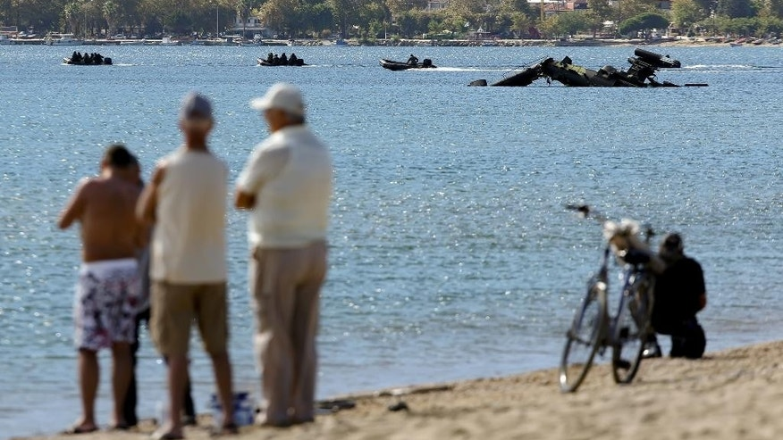 Local residents watch an Apache attack helicopter of the Greek army that crashed into the  sea as vessels with soldiers operate near the scene of the incident in the town of Asprovalta, northern Greece, Tuesday, Sept. 20, 2016. Greek authorities say two crew members were rescued after their helicopter suffered an engine failure and fell into the sea near the coast in northern Greece during a training exercise. (Kostas Villa/InTime News via AP)