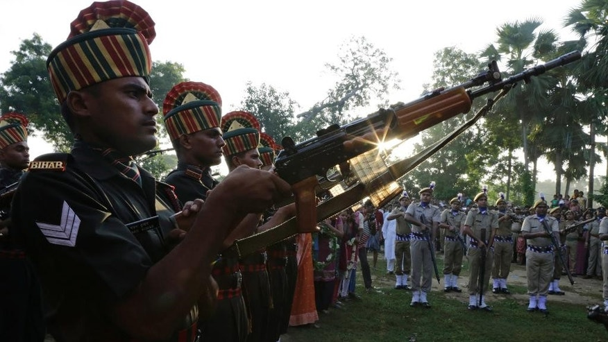 Indian army soldiers prepare to give a gun salute to their colleague Gangadhar Dalai, who was killed in a militant attack in Uri, Kashmir, prior to his cremation in Jamuna Balia village, west of Kolkata, India, Tuesday, Sept. 20, 2016. Early Sunday, fighters slipped into an army base in Indian-controlled Kashmir, killing at least 15 soldiers. (AP Photo/Bikas Das)