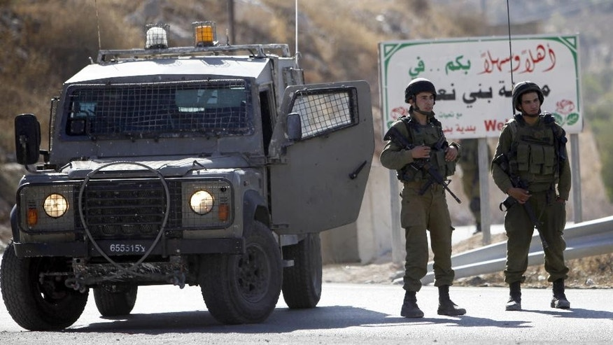 Israeli soldiers stand guard near the scene of an attack outside the West Bank city of Hebron on Tuesday.