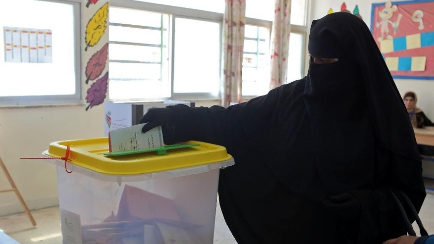 A Jordanian woman casts her ballot in parliamentary elections at a polling station in Amman Jordan, Tuesday, Sept. 20, 2016. Jordanians are voting for a new parliament under revised rules meant to strengthen political parties -- an election seen as a small step toward democratic reform. More than 4 million residents of the pro-Western monarchy are eligible to vote for a 130-member parliament, with 27 seats reserved for women, Christians and ethnic minorities. (AP Photo/Raad Adayleh)