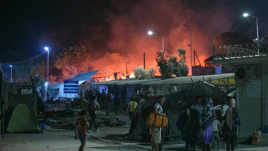 Migrants hold their belonging as a large fire burns inside the Moria refugee camp on the northeastern Greek island of Lesbos, late Monday, Sept. 19. 2016. Greek police say a large fire swept through the big camp for refugees and other migrants on the eastern Aegean island of Lesbos, forcing its evacuation. None of the more than 4,000 people in the Moria camp was reported injured in Monday's blaze, which damaged tents and prefabricated housing units. (AP Photo/Michael Schwarz)