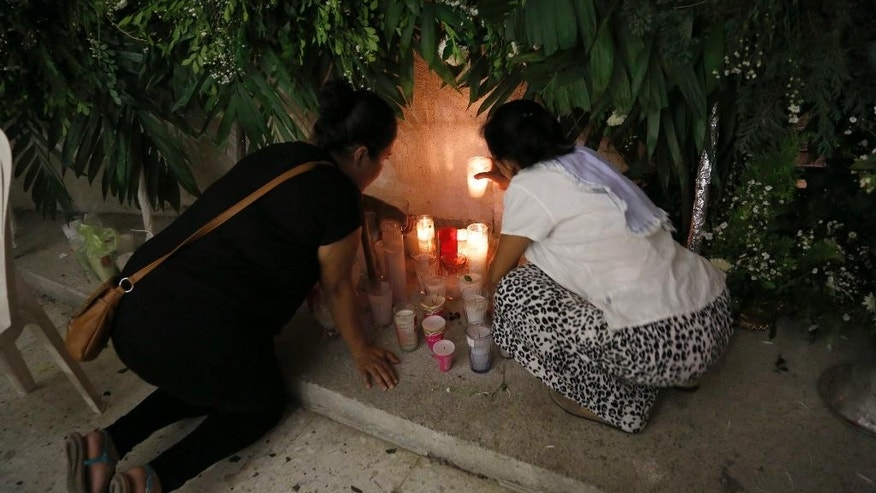 Women light candles in Our Lady of Fatima Church in Poza Rica, Veracruz state, Mexico, Tuesday, Sept. 20, 2016. Two of the church's priests were found dead on Monday, and were last seen Sunday. The bullet-ridden bodies of the priests were found on a roadside. (AP Photo/Marco Ugarte)