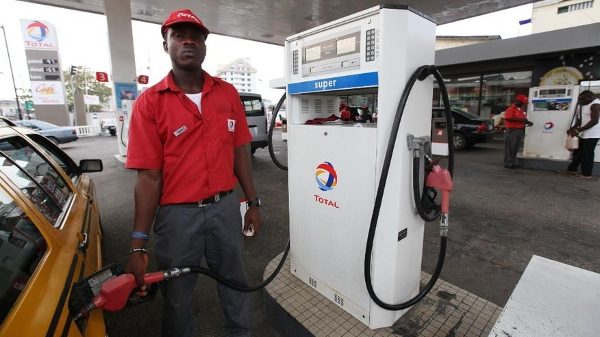 FILE- In this Monday, Nov. 19, 2012 file photo, a petrol attendant fills a car at a Total petrol station in Lagos, Nigeria. Officials say Nigeria is suing several oil majors for $12.7 billion of oil allegedly exported illegally to the United States between 2011 and 2014. The Federal High Court in Lagos begins the first hearing next week in cases filed against Nigerian subsidiaries of U.S. multinational Chevron, British-Dutch Shell, Italian ENI's Agip, France's Total and Brasoil of Brazilian Petrobas. (AP Photo/Sunday Alamba, File)