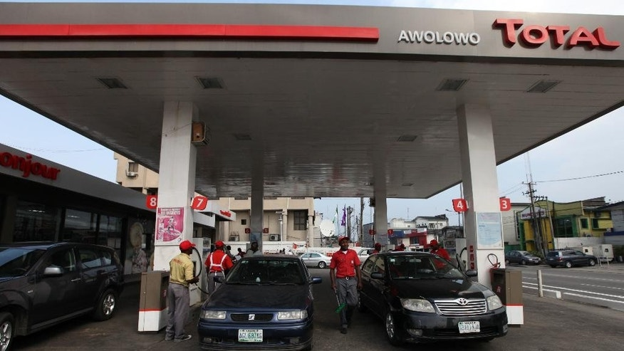 FILE- In this Monday, Nov. 19, 2012 file photo, petrol attendants filled cars at a Total petrol station in Lagos, Nigeria. Officials say Nigeria is suing several oil majors for $12.7 billion of oil allegedly exported illegally to the United States between 2011 and 2014. The Federal High Court in Lagos begins the first hearing next week in cases filed against Nigerian subsidiaries of U.S. multinational Chevron, British-Dutch Shell, Italian ENI's Agip, France's Total and Brasoil of Brazilian Petrobas. (AP Photo/Sunday Alamba, File)