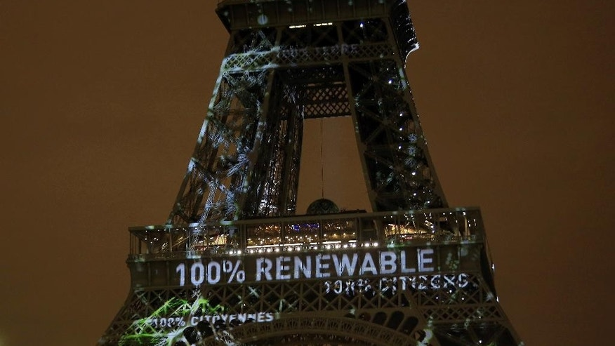 FILE- In this Sunday, Nov. 29, 2015 file photo, an artwork entitled 'One Heart One Tree' by artist Naziha Mestaoui is displayed on the Eiffel tower ahead of the 2015 Paris Climate Conference, in Paris. At least 20 countries are expected to formally join the Paris Agreement on climate change this week, greatly improving the pact's chances of coming into force just a year after it was negotiated in the French capital, U.N. officials say.  (AP Photo/Thibault Camus, File)
