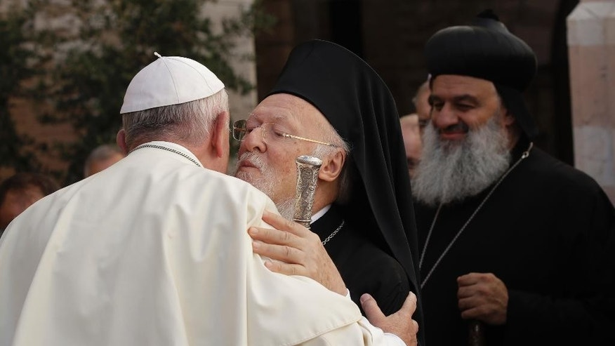 Pope Francis salutes Ecumenical Patriarch Bartholomew I as he arrives to the Holy Convent of Assisi, Italy, Tuesday, Sept. 20, 2016. Pope Francis has chatted with leaders and representatives of many religions at a gathering to pray for peace in Assisi, the home town of St. Francis. Christians will pray in St. Francis Basilica, while those from other religions will pray in different locations in the Umbrian hill town that for centuries has drawn those admiring the peace-advocating saint who abandoned wealth for an austere existence of preaching tolerance. (AP Photo/Alessandra Tarantino, Pool)