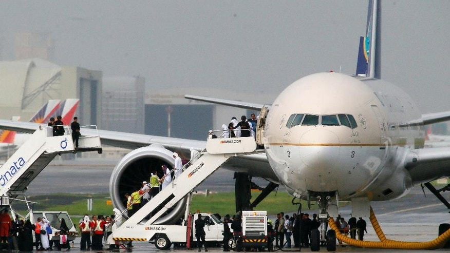 Passengers disembark from Saudi Arabian Airlines plane at the parallel runway of the Ninoy Aquino International Airport after it made a distress call shortly before landing Tuesday, Sept. 20, 2016 at suburban Pasay city south of Manila, Philippines. Philippine officials say the Saudi Arabian Airlines plane from Jeddah was placed in isolation after it touched down, but the flight crew later said they made a mistake in sending the emergency message. Manila airport manager Eddie Monreal said authorities deployed security forces around the aircraft as a precaution. Passengers were later allowed to disembark.(AP Photo/Bullit Marquez)