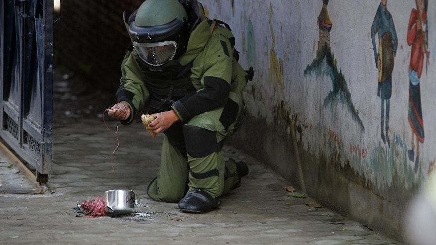 A Nepalese bomb squad member inspects a pressure cooker bomb after detonating it at the school in  Kathmandu, Nepal, Tuesday, Sept. 20, 2016. Police in Nepal say small bombs have exploded outside two schools in the capital, but no injuries and only minor damage were reported. Unexploded bombs were found at five other schools in the city. (AP Photo/Niranjan Shrestha)