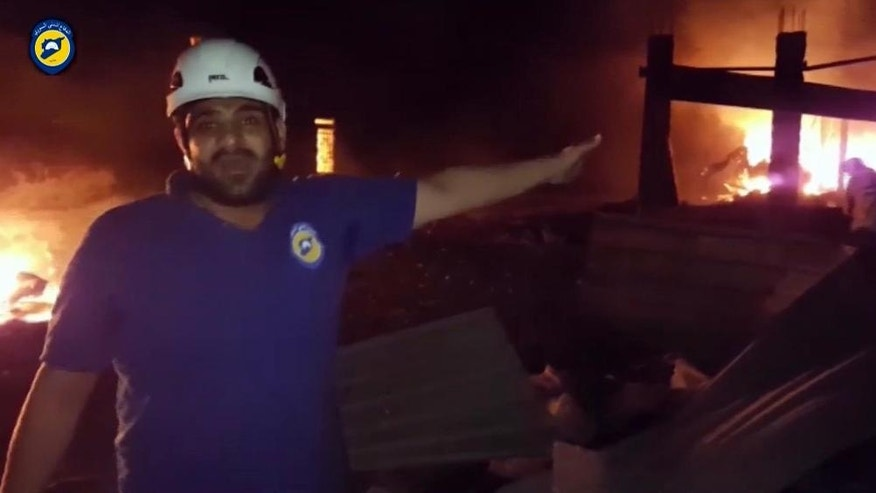 In this grab taken from video provided by the Syrian Civil Defence White Helmets, a member of the team describes the damage after an airstrike, in Aleppo, Syria, Monday, Sept. 19, 2016. At least 12 aid workers and truck drivers were reported killed in Syria late on Monday when their convoy was hit by airstrikes in Aleppo province. (Syrian Civil Defence White Helmets via AP)