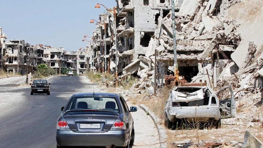 "Damaged buildings and rubble line a street in Homs, Syria, Sept. 19, 2016. Syria's military command has declared the U.S-Russian brokered cease-fire over, blaming the rebel groups for undermining it. In a statement Monday, the Syria military said ""the armed terrorist groups"" repeatedly violated the cease-fire which came into effect last week. (AP PHOTO)"