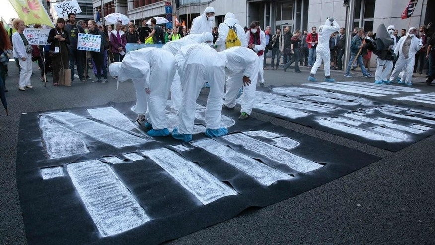 Greenpeace activists spray paint an anti-TTIP slogan on a street during a demonstration against international trade agreements in Brussels on Tuesday, Sept. 20, 2016. A demonstration was held in the European Quarter on Tuesday to protest against trade and investment deals such as TTIP and CETA. (AP Photo/Virginia Mayo)