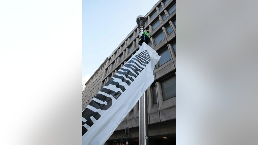 A Greenpeace activist attaches an anti-TTIP banner to a lamp post on a street during a demonstration against international trade agreements in Brussels on Tuesday, Sept. 20, 2016. A demonstration was held in the European Quarter on Tuesday to protest against trade and investment deals such as TTIP and CETA. (AP Photo/Virginia Mayo)