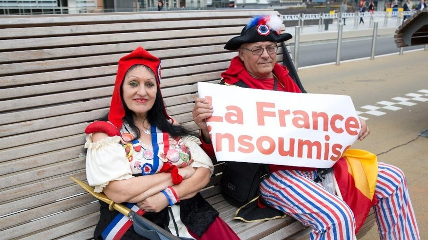 A couple in costume hold a banner which reads 'The Rebellious French' as they wait for the start of a demonstration against international trade agreements in Brussels on Tuesday, Sept. 20, 2016. A demonstration was held in the European Quarter on Tuesday to protest against trade and investment deals such as TTIP and CETA. (AP Photo/Virginia Mayo)