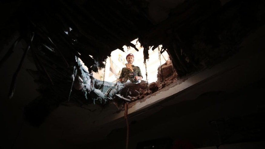 A soldier looks through a hole in a building damaged after an airstrike by Saudi-led coalition in Sanaa, Yemen, Tuesday, Sept. 20, 2016. (AP Photo/Hani Mohammed)