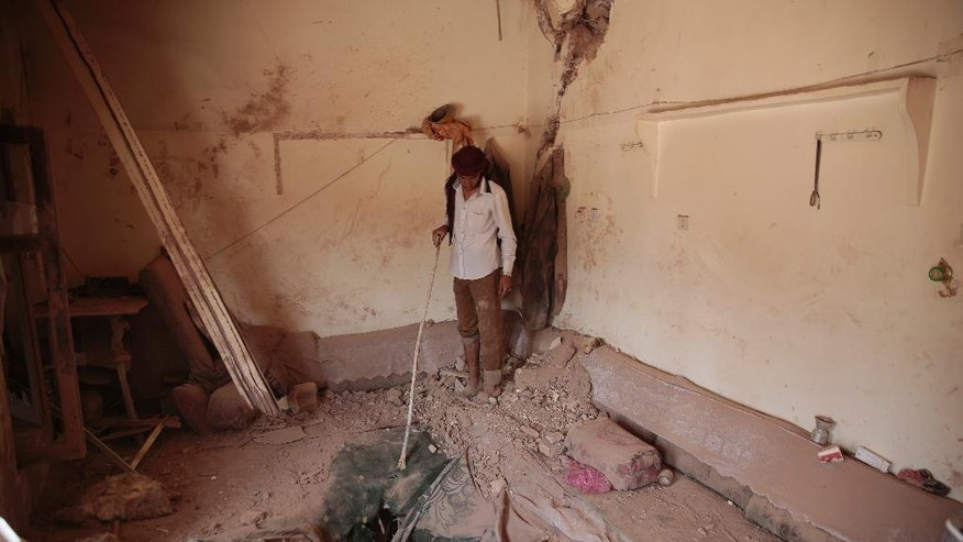 A Yemeni man inspects a damaged house after an airstrike by Saudi-led coalition in Sanaa, Yemen, Tuesday, Sept. 20, 2016. (AP Photo/Hani Mohammed)